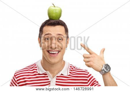 Happy guy pointing at an apple on his head isolated on white background