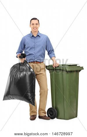 Young guy standing next to a garbage can and holding a trash bag isolated on white background