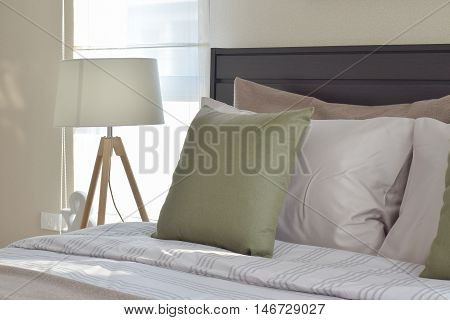 Modern Bedroom Interior With Green Pillow And Decorative Wooden Lamp On Bedside Table