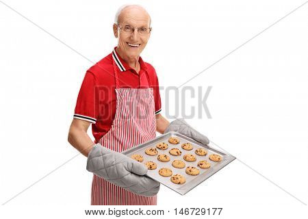 Cheerful mature man holding a tray of homemade cookies isolated on white background