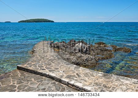 Pathway on the typical rocky beach in Istria, Croatian coast. Blue sea, sky and island on horizon.