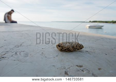 Macro shot of stone on foreground and humans silhouette on background on sunset