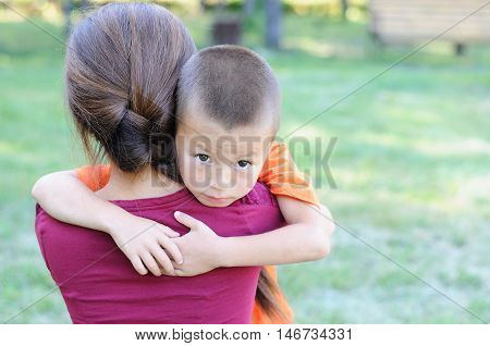 Caucasian little boy embracing mother with love