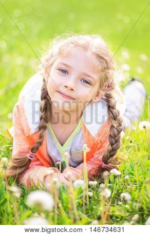 Cute little girl on the meadow in bright summer day