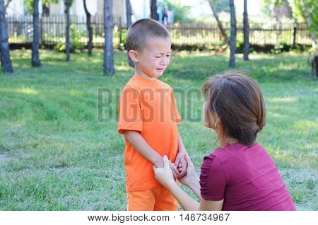 Mother calming down little crying boy outdoor