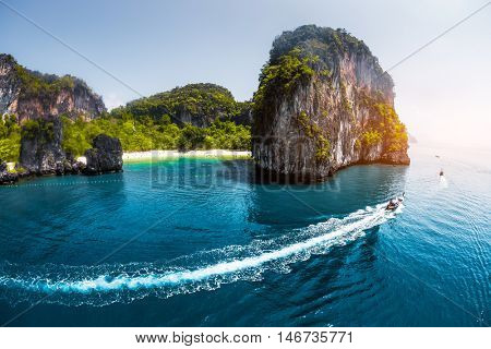 Aerial view of clear sea with traditional longtail thai boats and the white sandy beach hidden in mountains.