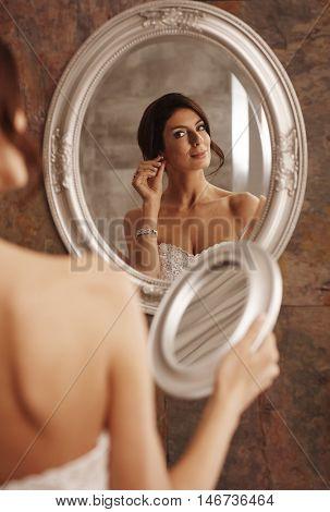 Bride inserting earrings on wedding-day, looking at herself in mirror.