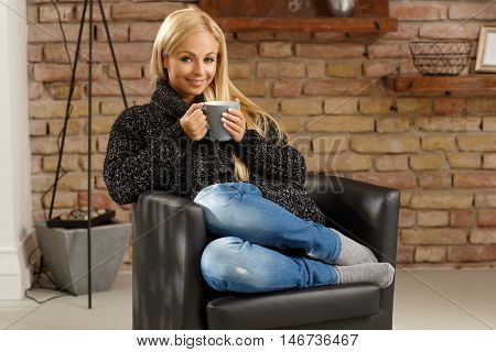 Happy woman drinking tea at home in armchair, smiling, looking at camera. Full size.