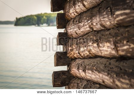 Wall of log house on the river bank close-up with a beautiful landscape in the background.