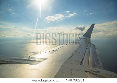Aircraft wing view of blue sky and sea from aircraft windows