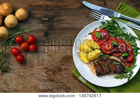 roasted beef filet mignon with potatoes and tomato arugula salad on a rustic wooden board with copy space view from above