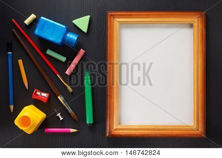 paint supplies and frame on black wooden background