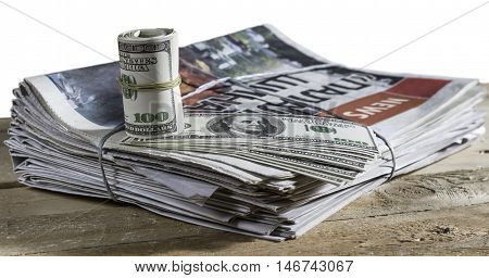 Money with print newspaper on the wooden table