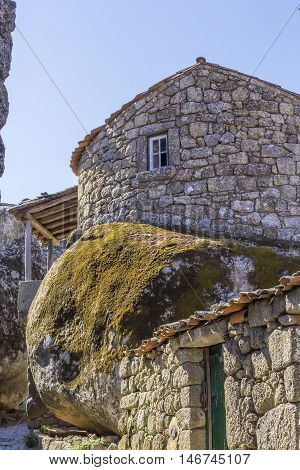 background landscape with an unusual stone house from a huge boulder wall in the village of Monsanto, District Kashtello Branco, Portugal