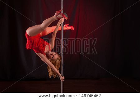 luxuriant sexy blonde in a red dress dancing on a pole. young girl on a pole dancer
