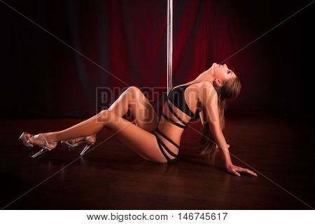 young sexy girl pole dancer posing on a red background. graceful flexible model pole