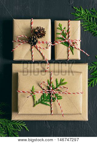 Christmas or New Year gifts collection decorated with fir twigs cones and traditional Xmas twine flat lay stylized photo