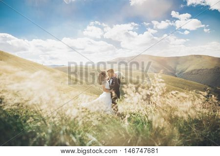 Young newly wed couple, bride and groom kissing, hugging on perfect view of mountains, blue sky.