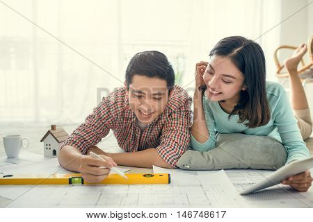 Close up of happy asian couple looking at blueprint at home