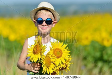 Adorable Boy In Sun Glasses And Hat With Sunflower On Field Outdoors