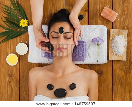 Black marble stone face massage in aroma spa. Beautician with female patient in wellness center. Professional therapy, relaxation procedure to beautiful indian girl in beauty parlor, top view on wood