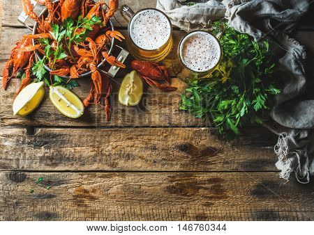 Two pints of wheat beer and boiled crayfish with lemon and parsley over old wooden rustic background, top view, copy space
