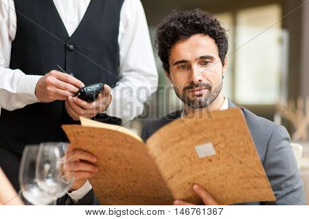 Man with menu in a restaurant making order