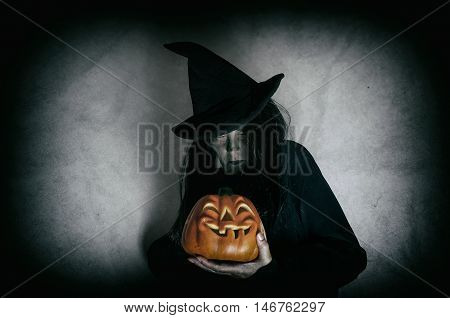Witch holding halloween pumpkin. Low key. Computer added dirt, scratches, grain and vignette.