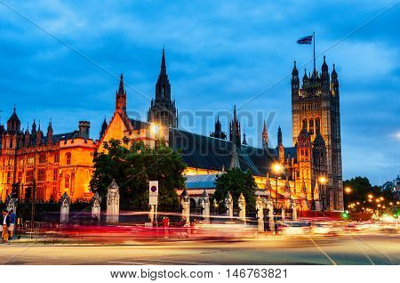 Palace of Westminster at night with car traffic and motion blurred people. Big Ben - Popular landmark in London UK