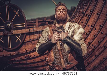 Serious viking warrior with axes standing near Drakkar on the seashore.