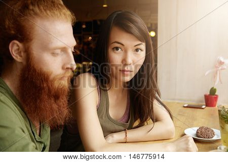 Multiethnic Couple. Cute Asian Girl Relaxing At Cafe With Her Hipster Boyfriend With Thick Red Beard