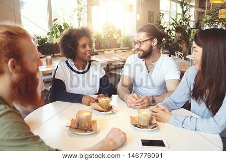 Multiethnic Group Of Young Ambitious People Sitting At Round Table At Coworking Space, Working Toget