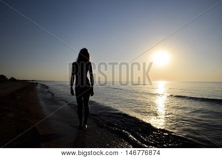 Silhouette Of A Girl Against The Sunset By The Sea