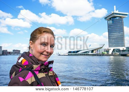 Young native dutch woman in the harbor from Amsterdam in the Netherlands