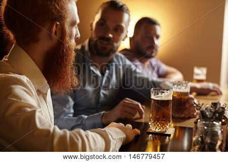 People, Leisure And Friendship. Old Friends Chatting To Each Other Drinking Lager Or Ale Sitting At