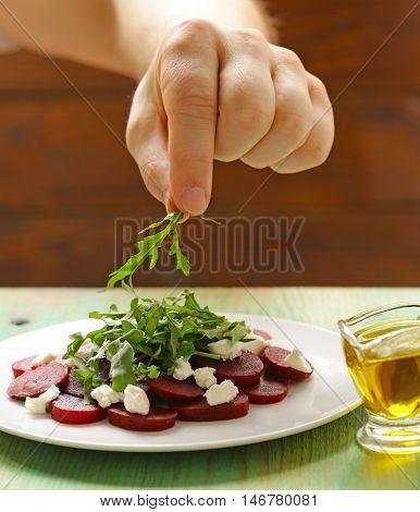 chef prepares salad of boiled beets, cheese and arugula