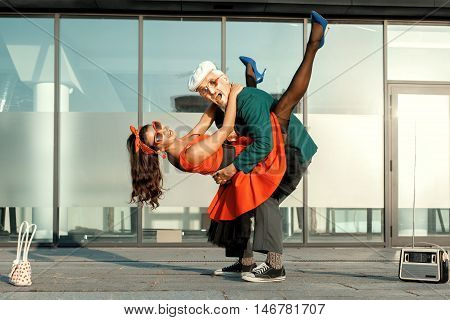 During the dance the young girl jumped on the old man.