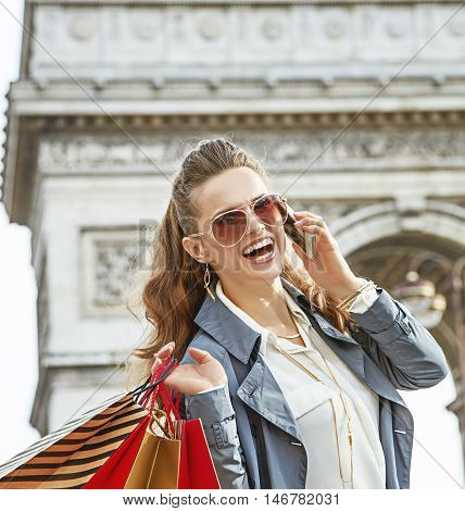 Woman With Shopping Bags In Paris, France Using Smartphone
