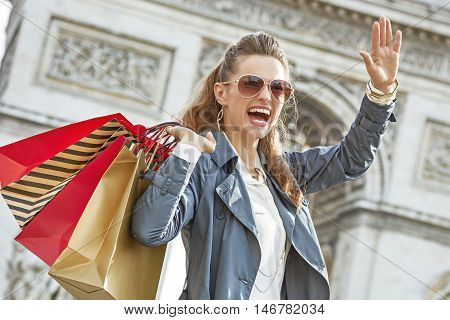 Smiling Woman With Shopping Bags In Paris, France Handwaving