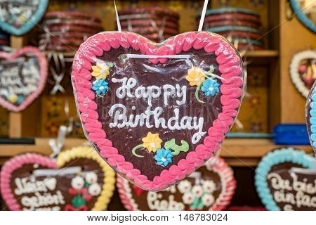 Colorful gingerbread sweetheart bearing the inscription Happy birthday / German Lebkuchen
