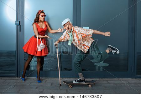 Funny old man riding a skateboard standing next to in surprise woman.