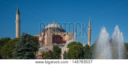 Aya Sophia against blue sky background. Green trees fountain and rainbow in foreground. Panoramic composition.