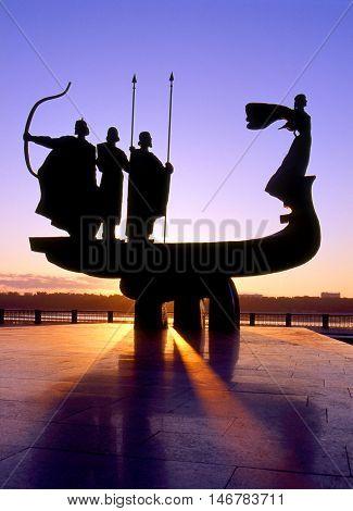 Founders of Kiev monument silhouette against sunrise scene.