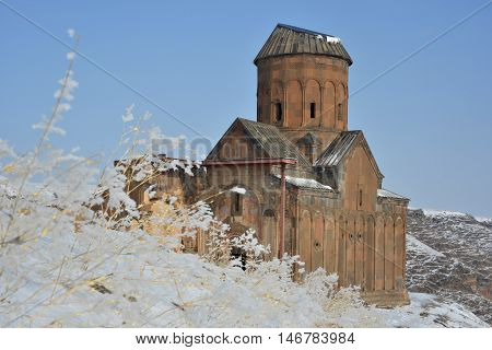 Old armenian church with skewed roof. Snow and frosted plants in foreground. Famous Saint Gregory (Tigran Honents) church in Ani (now - Turkey ).