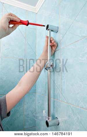 Plumbing repairs in bathroom close-up hands plumber tighten screw holder for shower using screwdriver.
