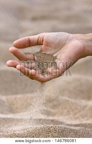 sand running through hand on the beach background