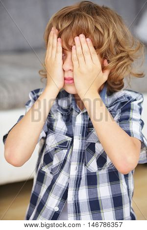 Boy playing hide and seek and holding hands over his eyes at home