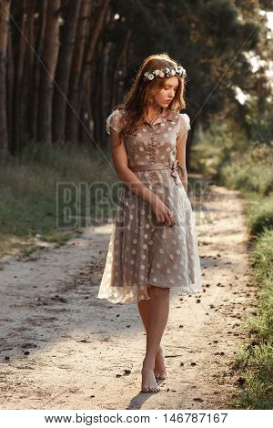 Young woman in wreath walking in forest barefoot. Beautiful girl in polka-dot dress relaxing in nature, she steps on path with pine cones, free space.