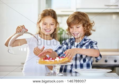 Two proud kids with their first homemade fruitcake in the kitchen