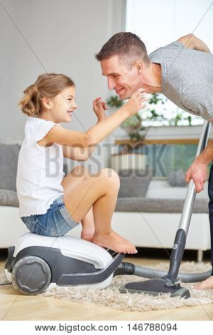 Happy father and smiling daughter with vacuum cleaner at home